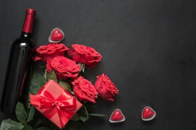 Valentinsgrußkarte mit romantischen roten rosen, weinflasche, herzen und roter geschenkbox auf holztisch. draufsicht mit platz.