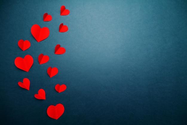 Valentinsgrußkarte mit rotem herzen auf blauem hintergrund, abstrakte, flache lage, draufsicht