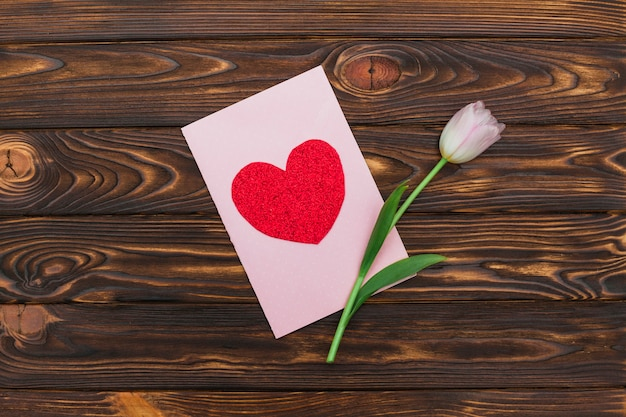 Valentinsgrußkarte und -blume auf hölzernem schreibtisch