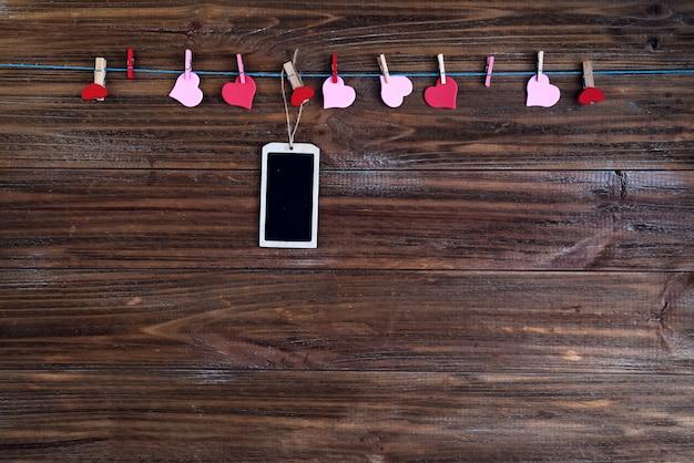 Valentinsgrußkreidebrett mit roten herzen auf braunem hölzernem hintergrund