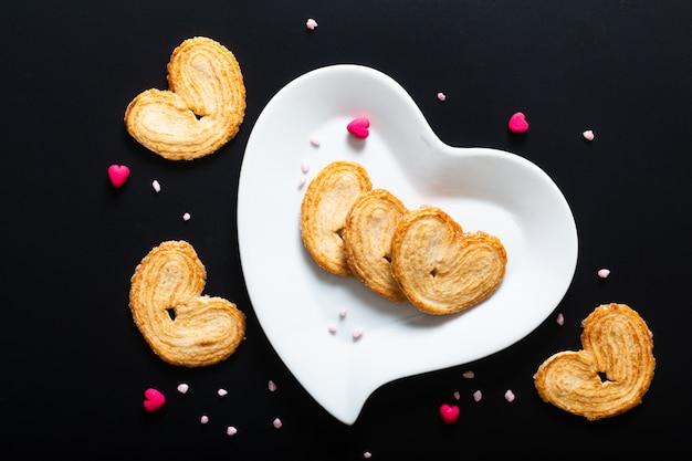 Valentinsgrußnachtischlebensmittelkonzept-blätterteigherzen in der weißen keramischen herzform auf schwarzem