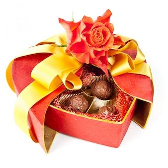 Valentinsgrußschokoladen und eine rose lokalisiert auf whit