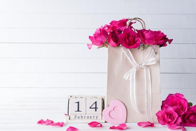 Valentinsgrußtag und liebeskonzept auf weißem hölzernem hintergrund.