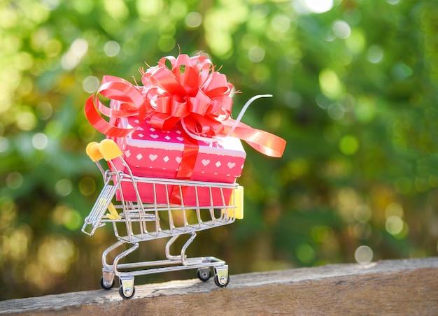 Valentinsgrußtageseinkaufen und geschenkboxgeschenkbox mit rotem band beugen auf einkaufswagen on-line-einkaufsferien