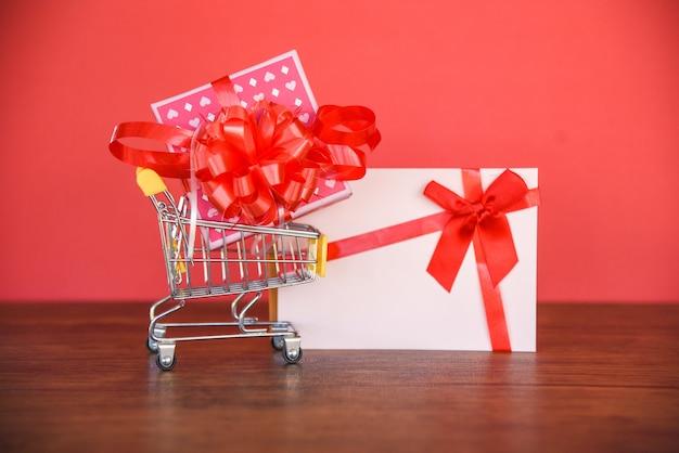 Valentinsgrußtageseinkaufen und geschenkkarte geschenkbox / rosa präsentkarton mit rotem bandbogen auf geschenkkarte