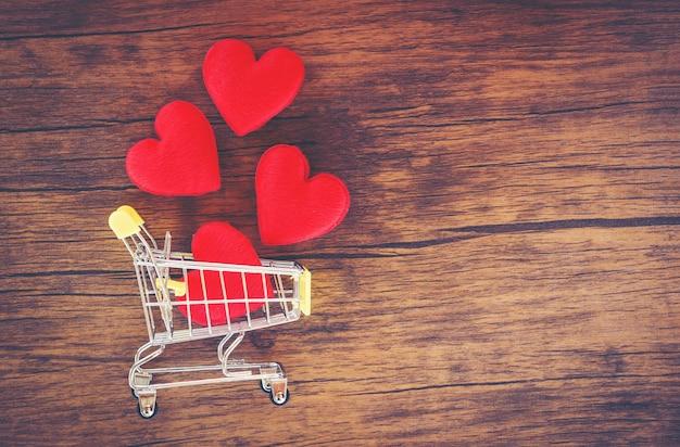 Valentinsgrußtageseinkaufen und rotes herz auf warenkorb lieben einkaufsfeiertag für liebe valentinsgrußtag auf hölzernem hintergrund