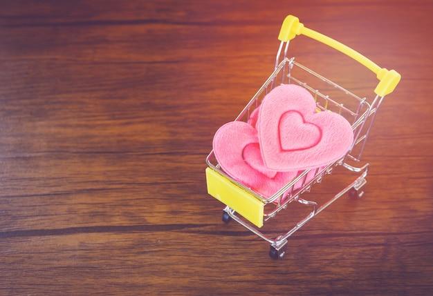 Valentinsgrußtageseinkaufsrosaherz auf warenkorb-liebe einkaufenfeiertag für liebe valentinsgrußtag auf hölzernem