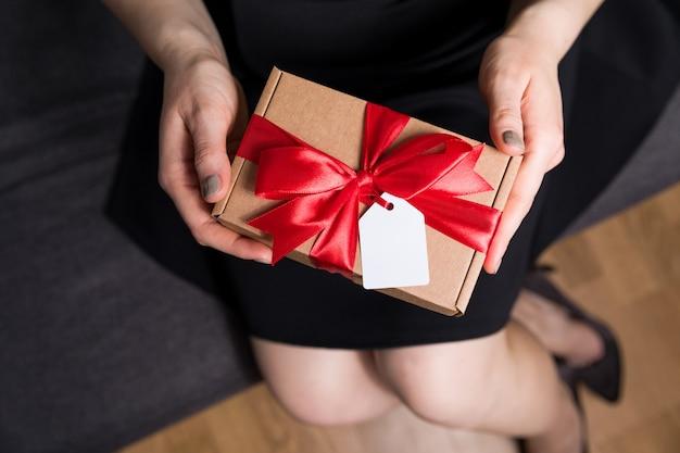 Valentinsgrußtagesgeschenk mit geschenkmarke und bogennahaufnahme - frau, die in den händen anwesend hält