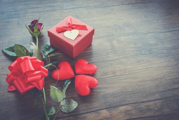 Valentinsgrußtagesgeschenkbox rot auf holz rote herz-valentinsgrußtagesrotrose blume und geschenkboxband beugen auf altem hölzernem