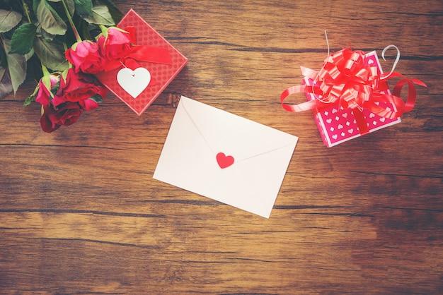 Valentinsgrußtagesgeschenkbox rot und rosa auf hölzerner valentinsgrußtageskarte-rotrosenblume und -geschenkbox