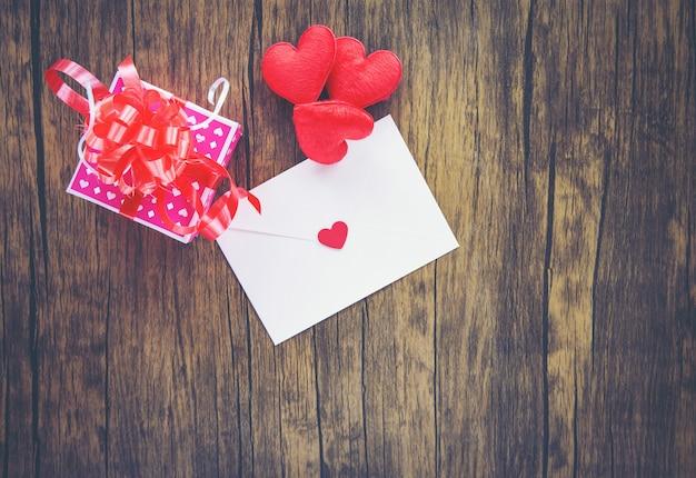 Valentinsgrußtagesgeschenkboxrosa auf hölzerner umschlagliebespost valentine letter card mit rotem herz-liebeskonzept