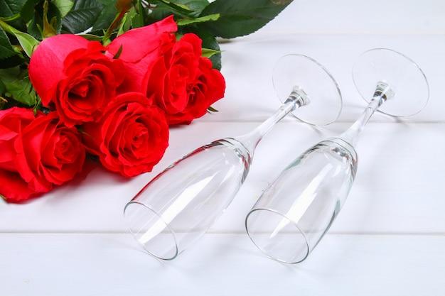 Valentinsgrußtagesgrußkarte, rote rosenblumen, weingläser und geschenkbox auf holztisch. draufsicht