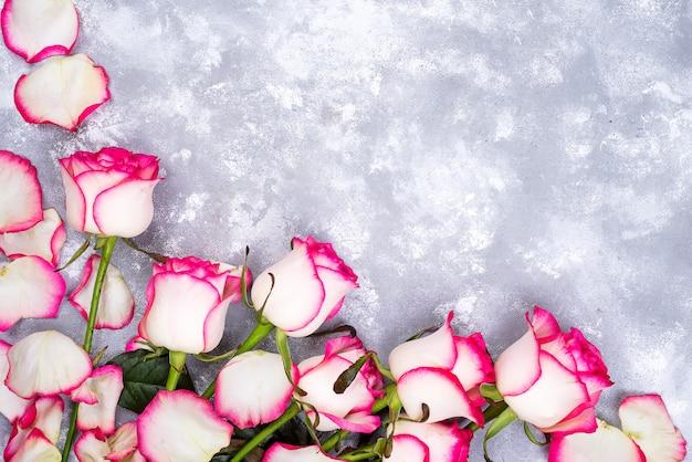 Valentinsgrußtageshintergrundrahmen mit rosafarbenem blumenblumenstrauß auf steinhintergrund.
