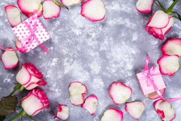 Valentinsgrußtageshintergrundrahmen mit rosafarbenem blumenblumenstrauß und geschenkbox auf stein
