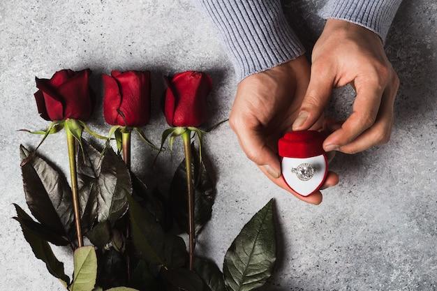 Valentinsgrußtagesromantische mannhand, die verlobungsring im kasten hält