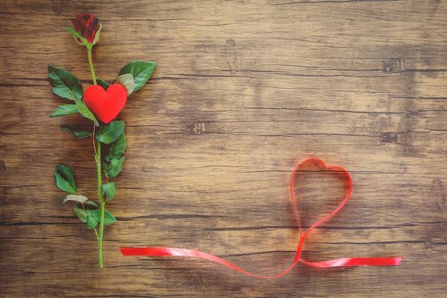 Valentinsgrußtagesrot-rosenblume auf hölzernem rotem herzen mit rosen und rotem bandherzen auf draufsichtkopienraum