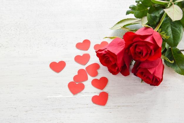 Valentinsgrußtagesrot-rosenblume auf weißem hölzernem hintergrund / kleinem rotem herzen der romantischen liebe