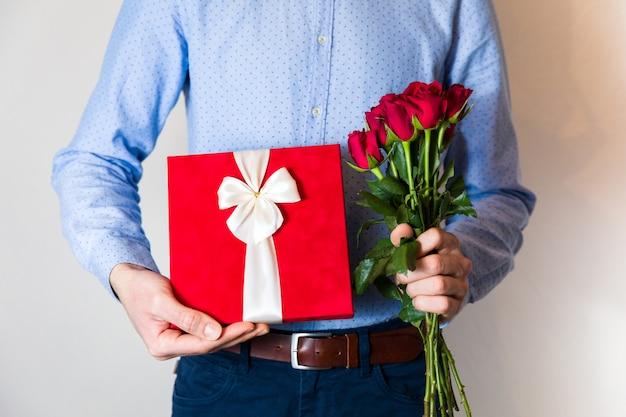 Valentinsgrußtagesüberraschung, liebe, gutaussehender mann, der romantisches geschenk hält und blumenstrauß der roten rosen.