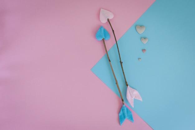 Valentinsgrußtageszweigpfeile auf rosa und blauem hintergrund mit herzen
