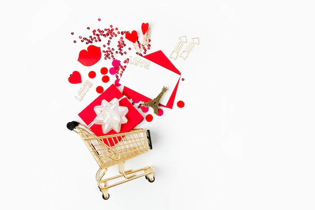 Valentinskarte, geschenk und konfetti in einem warenkorb auf weißem hintergrund. valentinstag einkaufen. flache lage, ansicht von oben