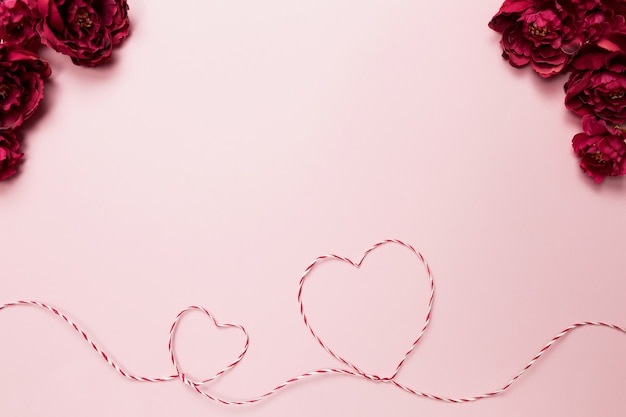 Valentinskarte. herzformen. rote weiße schnur oder seil. rosen. rosa hintergrund. hochwertiges foto