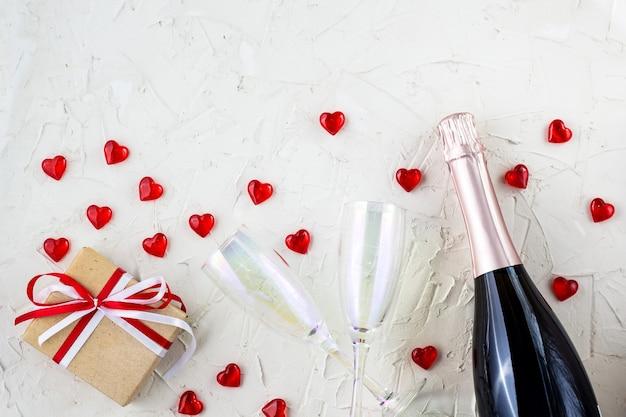 Valentinskarte mit champagnergläsern und flasche, herz und geschenk auf weißem hintergrund