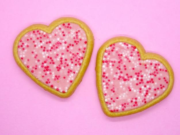 Valentinskekse, herzplätzchen in einem rosa hintergrund
