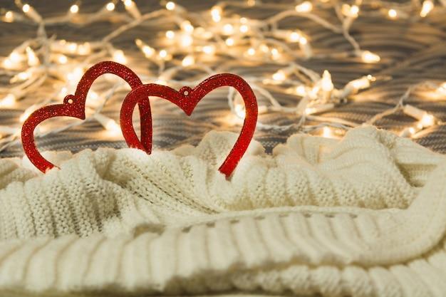Valentinskonzept mit herzen im warmen plaid mit lichtern