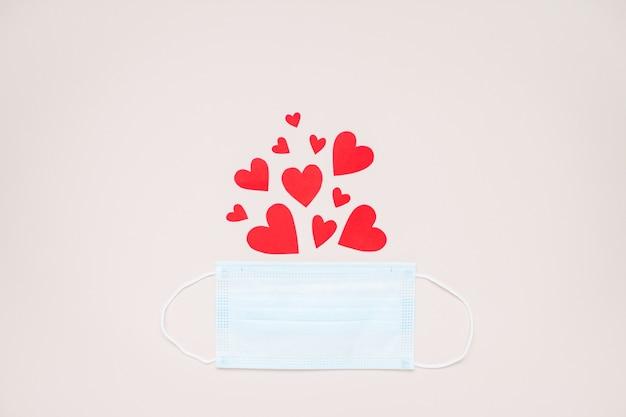 Valentinstag 2021. layout mit medizinischer schutzmaske und roten papierherzen. covid19