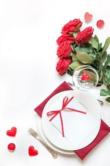 Valentinstag abendessen. romantisches gedeck mit roten rosen. von oben betrachten.