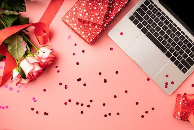 Valentinstag arbeitsbereich mit laptop-tastatur, konfetti, blumen und geschenkboxen