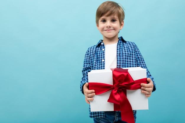 Valentinstag . attraktiver junge hält ein großes geschenk mit einem roten band auf einem hellblauen