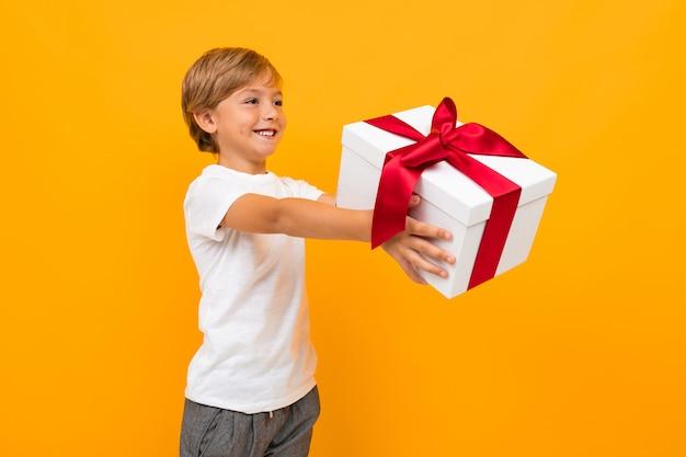 Valentinstag . attraktiver junge hält eine box mit einem geschenk mit einem roten band auf einem hellen gelb