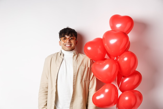 Valentinstag. aufgeregter junger mann, der lächelt, hoffnungsvoll aussieht, in der nähe von luftballons mit großen roten herzen steht und auf die wahre liebe am datum des liebenden wartet, weißer hintergrund.