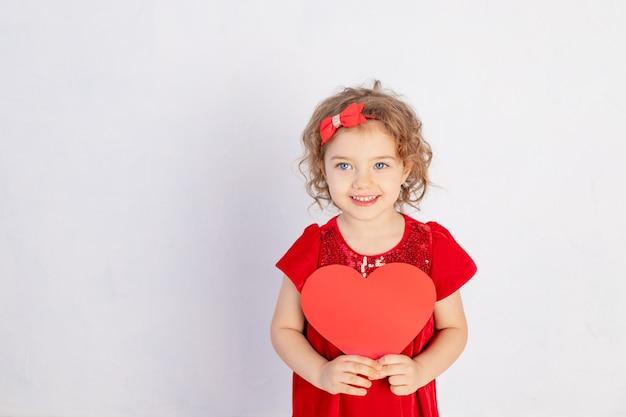 Valentinstag baby. kleines mädchen im roten kleid, das großes herz hält