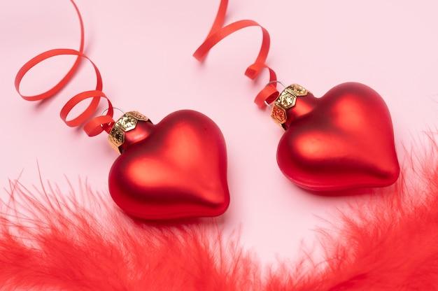Valentinstag banner bestehend aus roten glasherzen mit flauschigen rosa federn mit kopierraum für den text