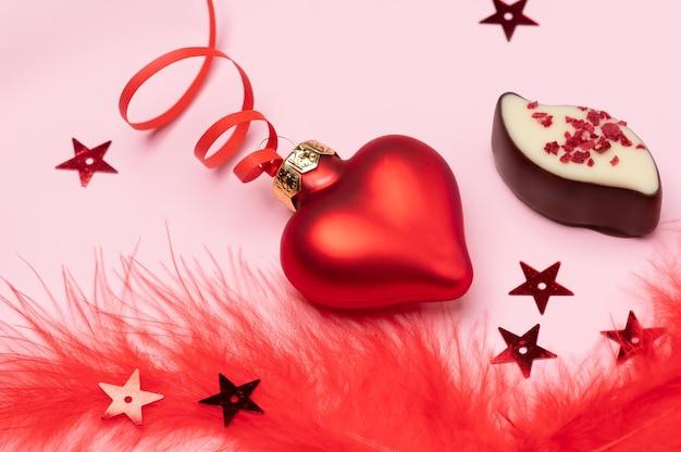 Valentinstag banner bestehend aus roten glasherzen mit flauschigen rosa federn und süßigkeiten mit kopienraum für den text