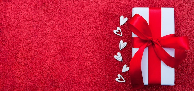 Valentinstag-banner mit geschenk und herzen auf einem roten glänzenden hintergrund kopieren raum