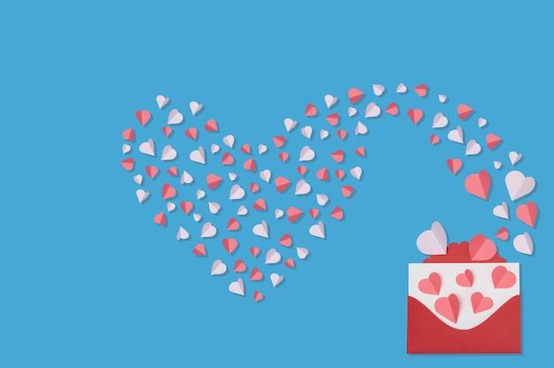Valentinstag-begrüßungskonzept mit umschlag und roten und rosafarbenen herzen auf blauer hintergrundoberansicht mit kopienraum für den text