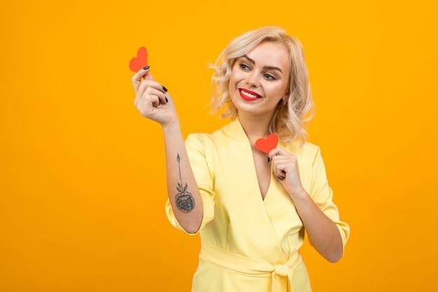 Valentinstag . blondes mädchen hält kleine valentinskarten in form von herzen auf einem gelb