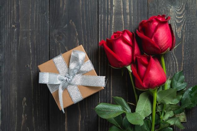 Valentinstag. blumenstrauß der rotrosenblume und des präsentkartons auf holztisch.