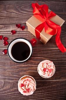 Valentinstag cupcakes frischkäse zuckerguss mit herz süßigkeiten, tasse kaffee und geschenkbox verziert. valentinstag konzept. speicherplatz kopieren. draufsicht.