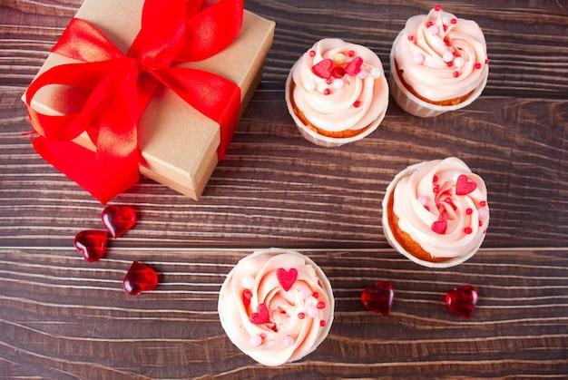 Valentinstag cupcakes frischkäse zuckerguss verziert mit herz süßigkeiten und geschenkbox auf holz