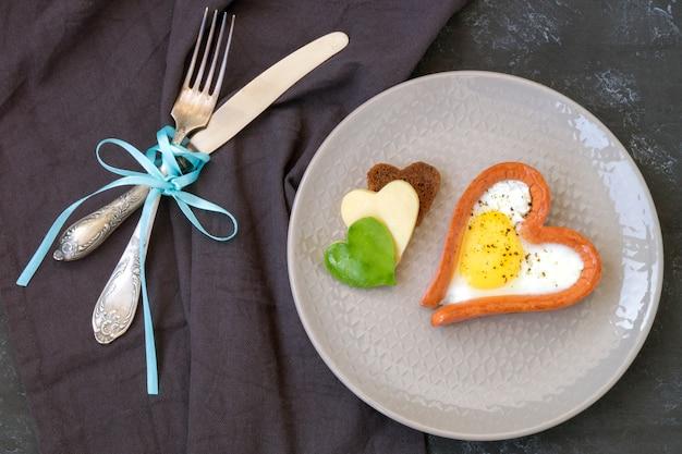 Valentinstag das frühstück besteht aus rührei mit herzförmigem brot.
