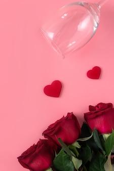 Valentinstag-datierungsgeschenk mit wein- und rosenkonzept auf rosa hintergrunddesignkonzept