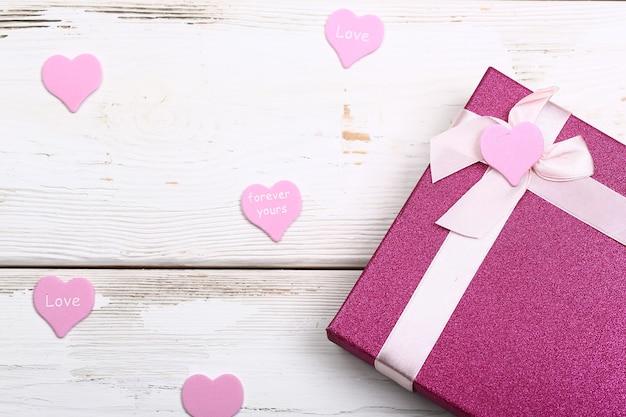 Valentinstag-design. rosa geschenkbox mit schleife auf weißem holzuntergrund