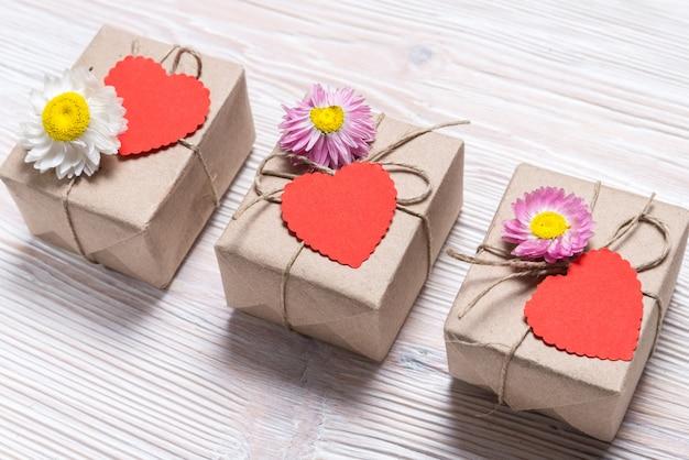 Valentinstag drei geschenkboxen auf hölzernem hintergrund
