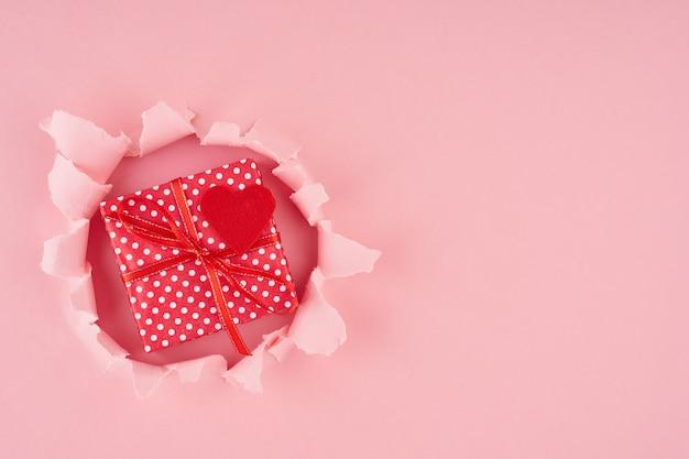 Valentinstag. ein zerrissenes loch und ein rotes herz mit geschenkbox im hellen rosa