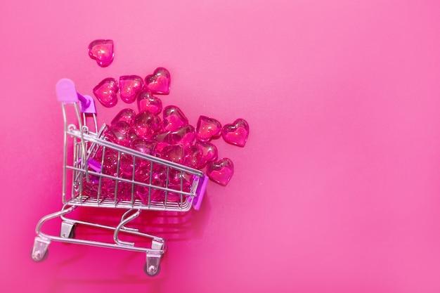 Valentinstag, endlose liebe oder konzept für besondere anlässe: draufsicht auf rote herzen, die aus einem einkaufswagen verschüttet wurden. isoliert auf rosa hintergrund. speicherplatz kopieren.