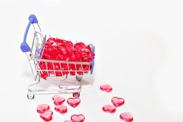 Valentinstag, endlose liebe oder konzept für besondere anlässe: draufsicht auf rote herzen, die aus einem einkaufswagen verschüttet wurden. isoliert auf weißer oberfläche. speicherplatz kopieren.